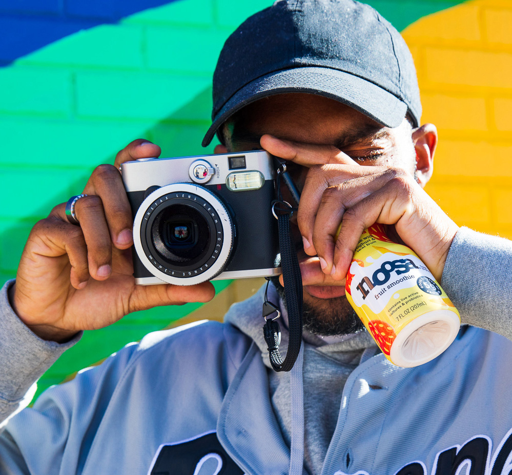 person holding camera and noosa bottle